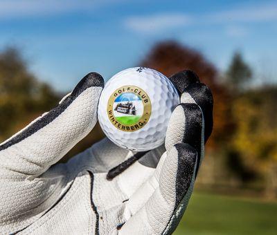 Golfer mit Handschuhen hält Golfball in den Händen