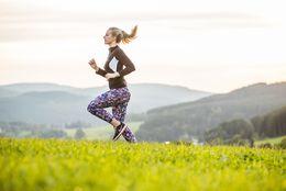 Eine Läuferin auf einer grünen Wiese in der Ferienwelt Winterberg