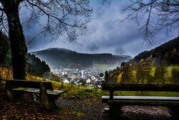 Zwei Bänke vor landschaftlichem Panorama oberhalb einens Dorfes