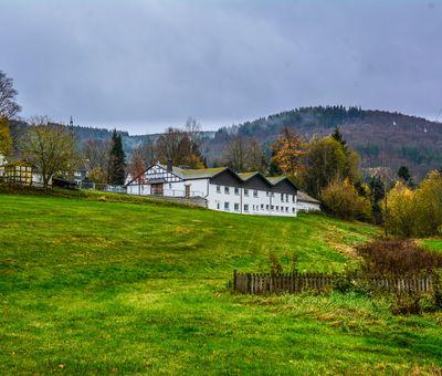Im Hintergrund einer grünen Wiese sieht man die Schützenhalle von Altenfeld