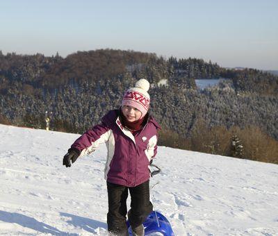 Mädchen zieht einen Schlitten den Berg hinauf