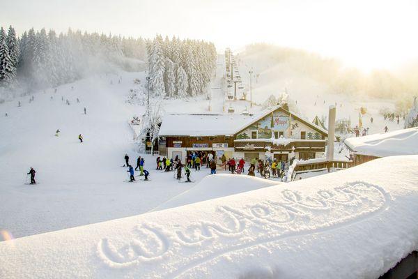 Winterberg in Schnee geschrieben, dahinter Piste und Hütte