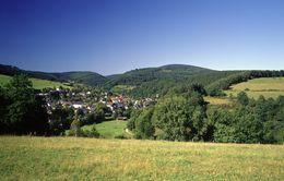 Ein Dorf inmitten einer grünen hügeligen Landschaft