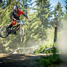 Biker springt mit seinem Rad auf einer Downhillstrecke über einen Erdhügel