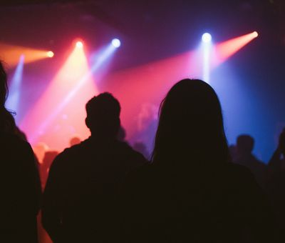 Die dunklen Umrisse von Menschen in einer Disco, vor ihnen strahlt Partybeleuchtung von der Decke