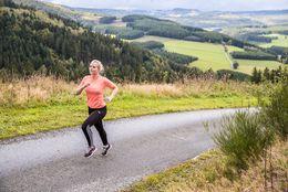Eine Läuferin auf einem Asphaltweg in der Natur der Ferienwelt Winterberg