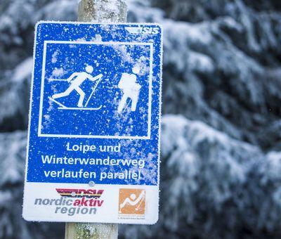 Schild für den Wegweiser der Langlaufloipen, blau mit weißem Langläufer