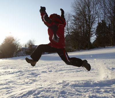 Ein Junge springt durch den Schnee