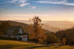Landschaftsaufnahme mit einem Haus über der Bergen