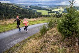 Zwei Läufer auf einem Schotterweg in der Ferienwelt Winterberg