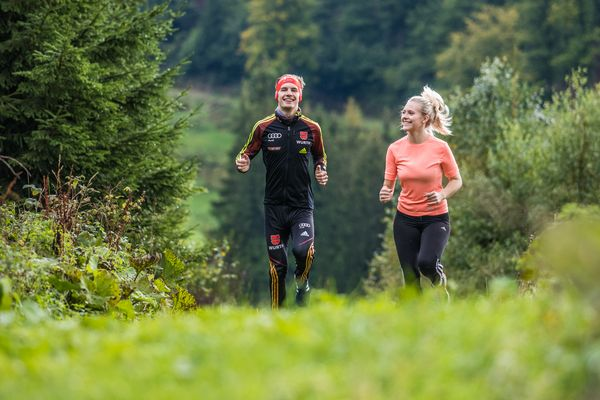 Zwei Läufer auf einem Feldweg zwischen den Wäldern der Ferienwelt Winterberg, Frontalansicht