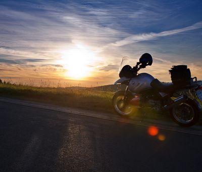 Ein Motorrad steht auf einem Weg, dahinter der Sonnenuntergang